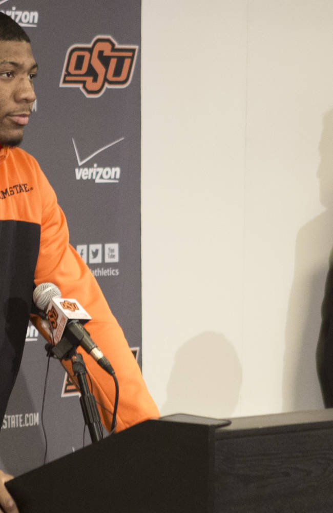This photo provided by Oklahoma State University Athletics shows Oklahoma State basketball player Marcus Smart, left, addressing the media at a news conference in Stillwater, Okla., Sunday, Feb. 9, 2014, in regard to an altercation during an NCAA college basketball game the day before. Smart was suspended three games by the Big 12 for shoving a fan. Oklahoma State athletic director Mike Holder, bottom right, and Oklahoma State basketball coach Travis Ford look on