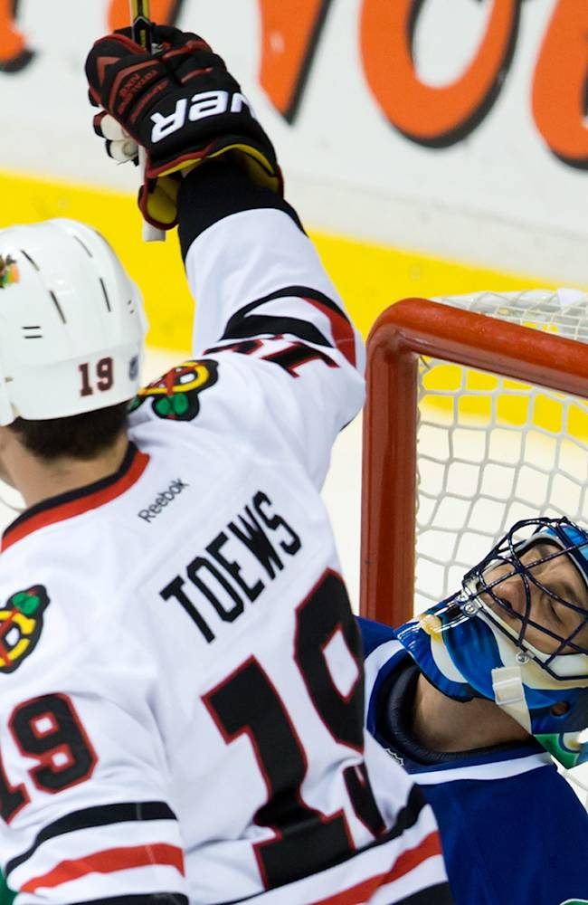 Vancouver Canucks' goalie Roberto Luongo, right, reacts as Chicago Blackhawks' Jonathan Toews celebrates a goal by teammate Andrew Shaw, not seen, during third period NHL hockey action in Vancouver, British Columbia Saturday Nov. 23, 2013