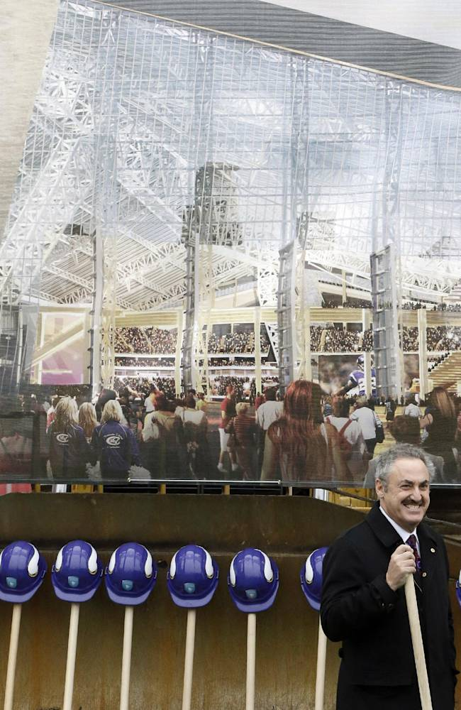 In this Dec. 3, 2013, file photo, a large rendering of the new Minnesota Vikings stadium hangs behind Vikings owner Zygi Wilf, right, as he waits to shovel the first dirt during one of several ceremonial dirt tosses at a groundbreaking ceremony for the Vikings newNFL football stadium in Minneapolis. Minnesota's Supreme Court on Tuesday, Jan. 21, 2014, dismissed a lawsuit challenging the funding plan for a new Vikings football stadium, eliminating a legal obstacle that threatened a last-minute derailment of the project. The lawsuit was filed Jan. 10 by Doug Mann, an activist and former Minneapolis mayoral candidate who argued the stadium funding plan was unconstitutional. The state's highest court disagreed