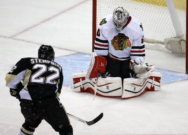 Pittsburgh Penguins' Lee Stempniak (22) puts the puck behind Chicago Blackhawks goalie Corey Crawford (50) for a goal in the first period of an NHL hockey game in Pittsburgh, Sunday, March 30, 2014