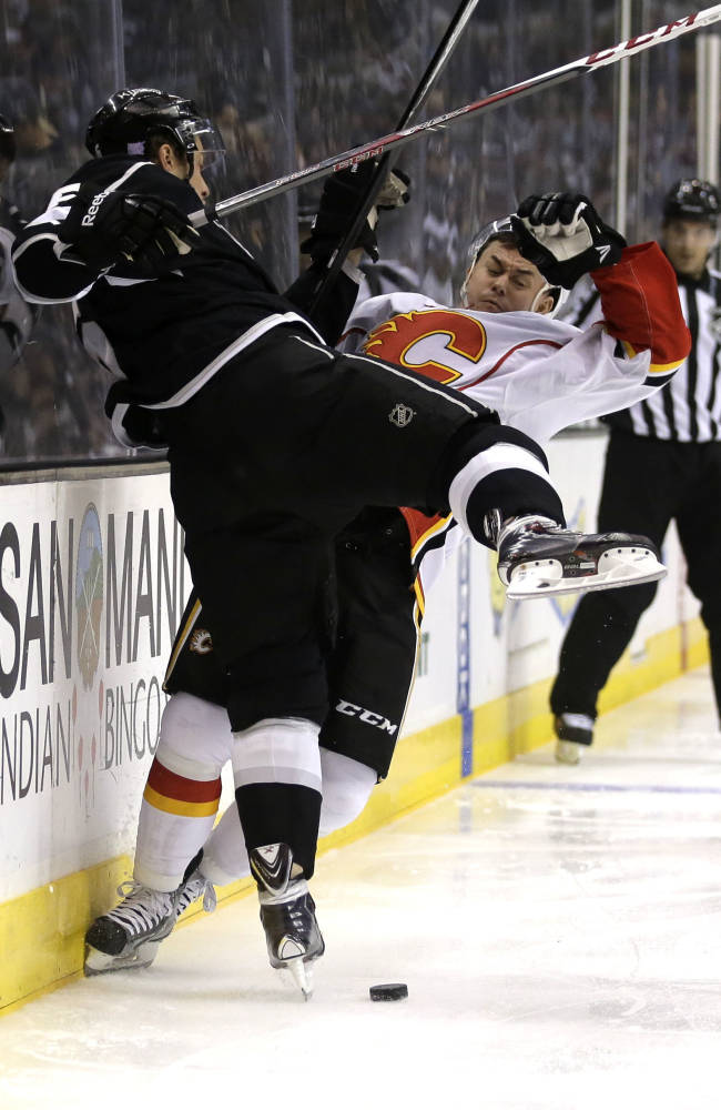 Los Angeles Kings defenseman Jake Muzzin, left, checks Calgary Flames left wing Jiri Hudler during the first period of an NHL hockey game in  Los Angeles, Monday, Oct. 21, 2013
