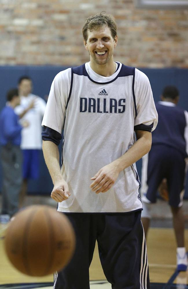 Dallas Mavericks' Dirk Nowitzki (41) of Germany smiles as he practices free throws at  NBA basketball training camp Thursday, Oct. 3, 2013, in Dallas