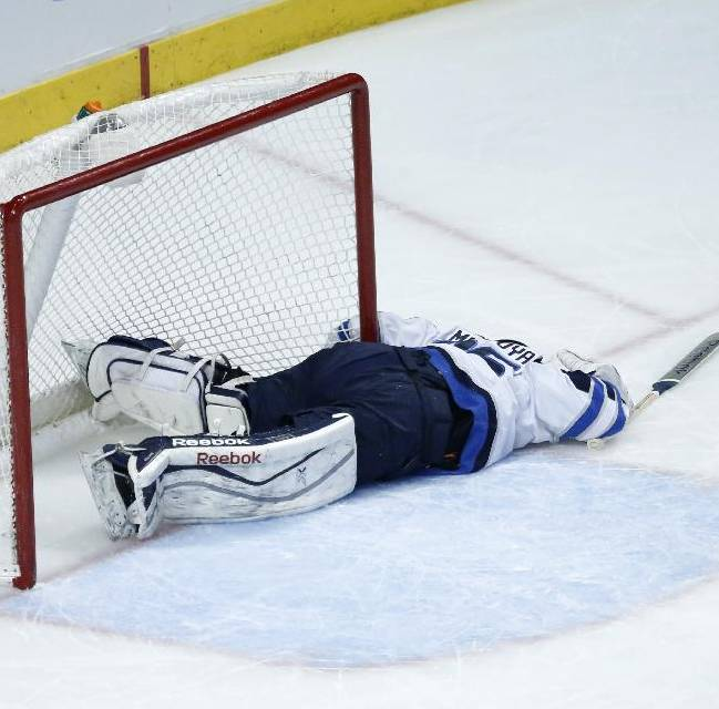Winnipeg Jets goalie Al Montoya lies on the ice after a collision with Chicago Blackhawks right wing Marian Hossa during the first period of an NHL hockey game Sunday, Jan. 26, 2014, in Chicago