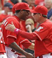 Cincinnati Reds relief pitcher Aroldis Chapman, left, is congratulated by manager Bryan Price after Chapman earned his first save of the year in the Reds 4-1 win over the Colorado Rockies in a baseball game, Sunday, May 11, 2014, in Cincinnati. Chapman was making his first appearance since being hit in the head with a line drive in spring training. (AP Photo/Al Behrman)