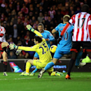 Sunderland's Adam Johnson, left, scores his goal past Tottenham Hotspurs' goalkeeper Hugo Lloris, center, during their English Premier League soccer match at the Stadium of Light, Sunderland, England, Saturday, Dec. 7, 2013