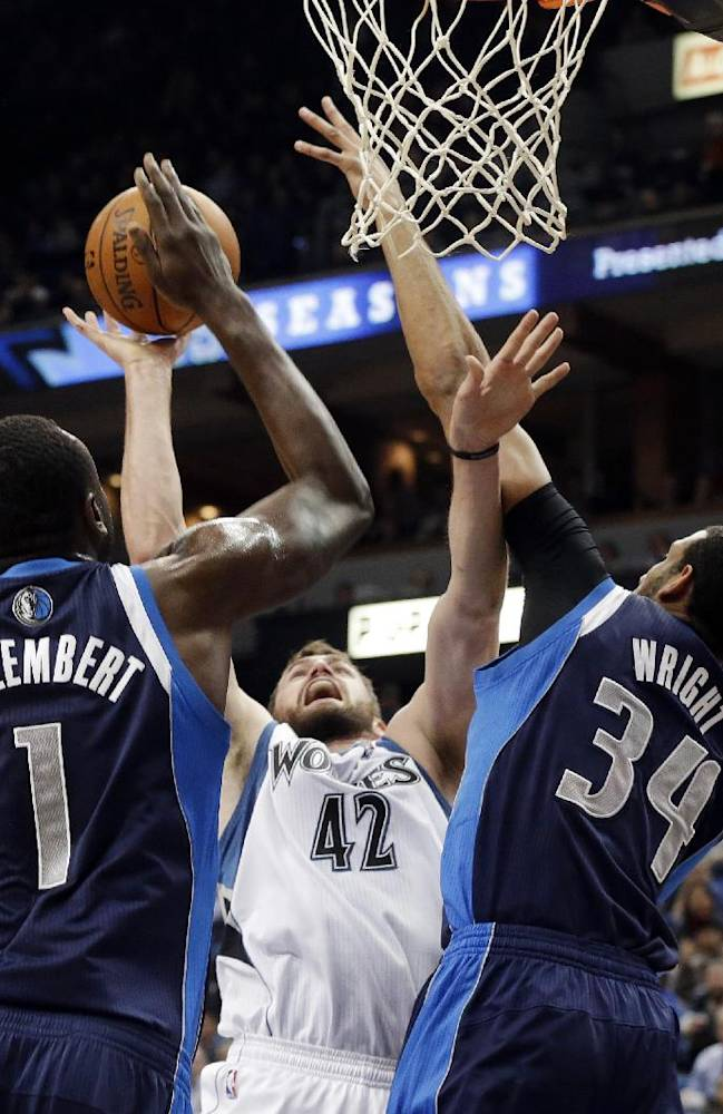 Minnesota Timberwolves' Kevin Love, center, is double teamed by Dallas Mavericks' Samuel Dalembert, left, of Haiti, and Brandan Wright  in the first quarter of an NBA basketball game, Monday, Dec. 30, 2013, in Minneapolis