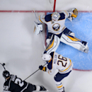 Los Angeles Kings right wing Dustin Brown, lower left, tries to get a shot in on Buffalo Sabres goalie Jhonas Enroth, top, of Sweden, as left wing Matt Moulson defends during the third period of an NHL hockey game, Thursday, Oct. 23, 2014, in Los Angeles.