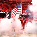 Louisiana-Lafayette defensive lineman Justin Hamilton (6) carries an American flag out to the field before the New Orleans Bowl NCAA college football game against Nevada in New Orleans, Saturday, Dec. 20, 2014 The Associated Press
