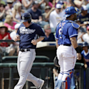 San Diego Padres' Jedd Gyorko scores as Texas Rangers catcher Geovany Soto, right, stands near during the first inning of a spring exhibition baseball game Sunday, March 23, 2014, in Surprise, Ariz The Associated Press