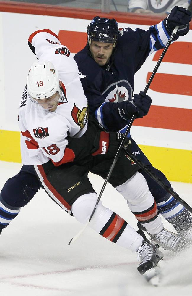 Ottawa Senators' Jim O'Brien (18) and Winnipeg Jets' Ian White (7) fight for the puck deep in the Jets' zone during the first period of a preseason NHL hockey game in Winnipeg on Sunday, Sept. 15, 2013