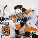 Philadelphia Flyers center Sean Couturier, center (14), is mobbed by teammates after his goal against the San Jose Sharks during the first period of an NHL hockey game Tuesday, Dec. 2, 2014, in San Jose, Calif The Associated Press