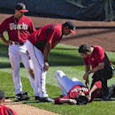 Arizona Diamondbacks pitcher Trevor Cahill lies on the field after jamming his knee covering first base, during an exhibition baseball game against the Cleveland Indians on Tuesday, March 11, 2014, in Scottsdale, Ariz The Associated Press