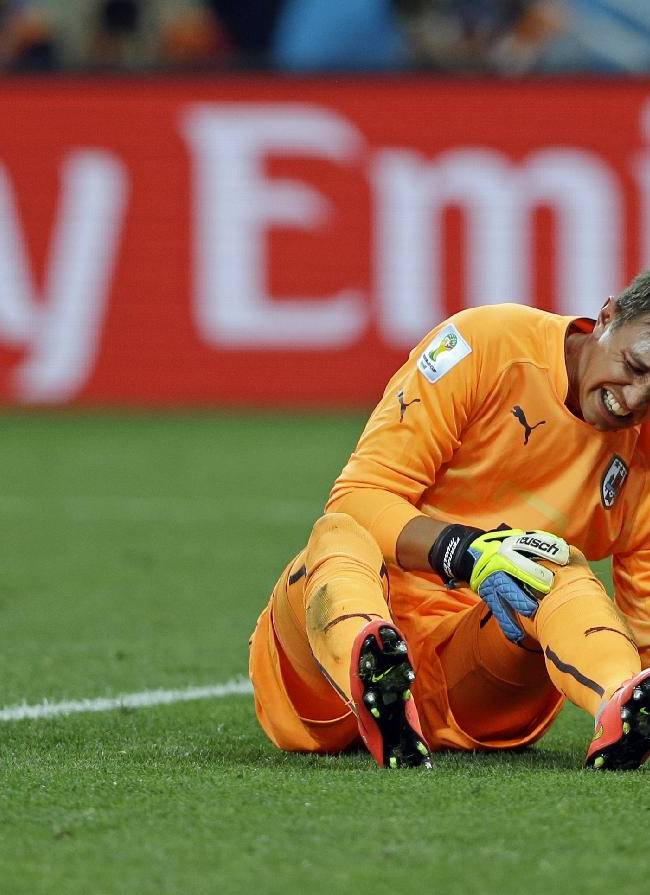 Uruguay's goalkeeper Fernando Muslera grimaces after England's Danny Welbeck slid into his knee with his cleats during the group D World Cup soccer match between Uruguay and England at the Itaquerao Stadium in Sao Paulo, Brazil, Thursday, June 19, 2014