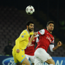 Napoli's Raul Albiol, left, and Arsenal's Olivier Giroud go for the ball during a Champions League, group F, soccer match between Napoli and Arsenal, at the Naples San Paolo stadium, Italy, Wednesday, Dec. 11, 2013