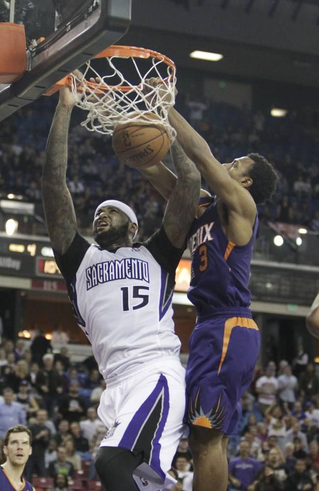 Sacramento Kings center DeMarcus Cousins, left, stuffs against Phoenix Suns guard Ish Smith during the fourth quarter of an NBA basketball game in Sacramento, Calif., Tuesday, Nov. 19, 2013.  The Kings won 107-104
