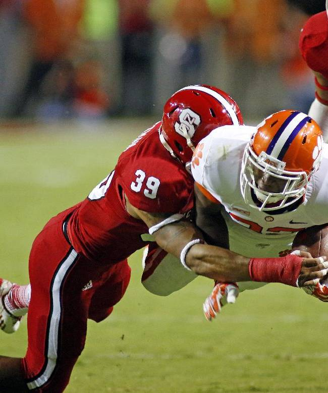 Clemson's D.J. Howard, center, dives for extra yards in the grasp of North Carolina State's Brandon Pittman (39) with NC State's Niles Clark (21) nearby during the second half of an NCAA college football game in Raleigh, N.C., Thursday, Sept. 19, 2013. Clemson won 26-14