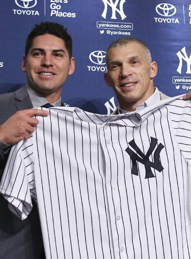 In this Dec. 13, 2013 file photo, Jacoby Ellsbury, left, and New York Yankees manager Joe Girardi hold Ellsbury's jersey during a news conference at Yankee Stadium in New York. The outfielder agreed to a $153 million seven-year contract. While the Yankees set another salary record, the Houston Astros had the lowest average in the major leagues in 14 years and the attention of the players' union. The overall big league average rose 5.4 percent this season to a record $3.39 million, according to the annual report released Wednesday, Dec. 18, 2013,  by the Major League Baseball Players Association