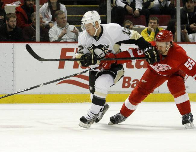 Pittsburgh Penguins' Chuck Kobasew (12) tries to keep Detroit Red Wings' Niklas Kronwall (55), of Sweden, off the puck during the first period of an NHL hockey game on Saturday, Dec. 14, 2013, in Detroit