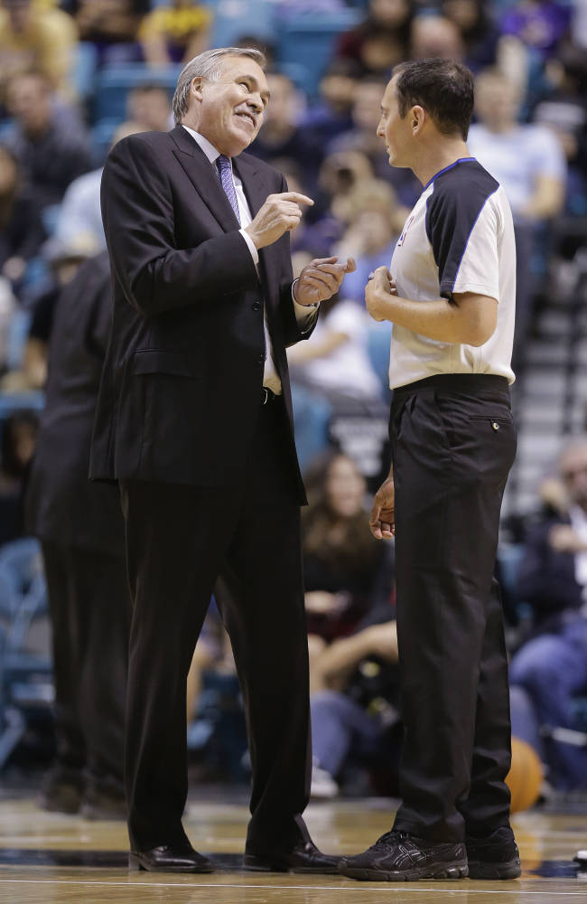 Los Angeles Lakers coach Mike D'Antoni talks with referee Marat Kogut (68) during a time out of a preseason NBA basketball game against the Sacramento Kings, Thursday, Oct. 10, 2013, in Las Vegas. The Kings won 104-86