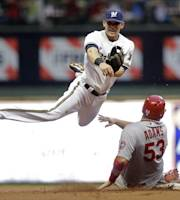 St. Louis Cardinals' Matt Adams breaks up a double play as Milwaukee Brewers' Scooter Gennett makes a late throw to first on a ball hit by David Freese during the second inning of a baseball game Tuesday, Aug. 20, 2013, in Milwaukee. (AP Photo/Morry Gash)