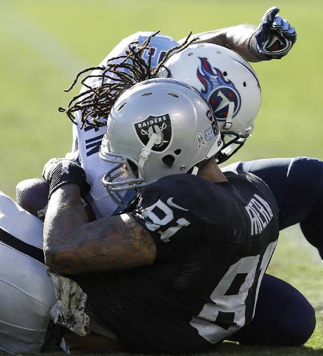 Oakland Raiders tight end Mychal Rivera (81) is hit by Tennessee Titans free safety Michael Griffin during the second quarter of an NFL football game in Oakland, Calif., Sunday, Nov. 24, 2013. Rivera was taken to the locker room and is being evaluated for a head injury after the play