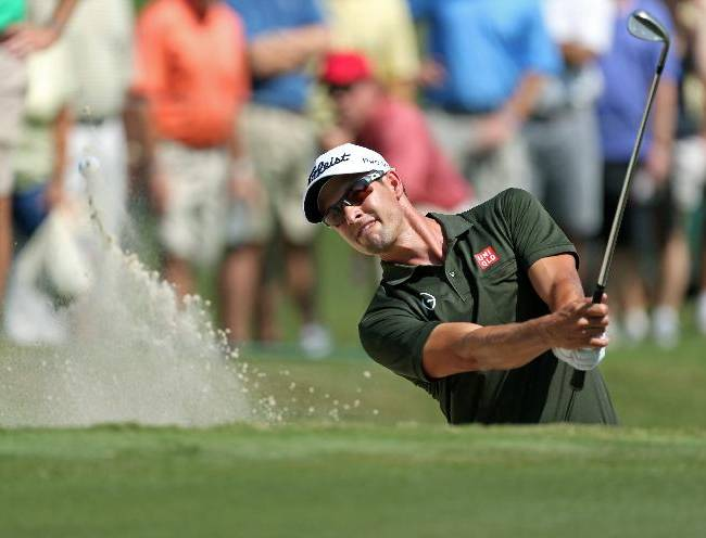 Adam Scott follows through on a bunker shot on the first green during round one of the 2013 Tour Championship golf tournament at East Lake Golf Club, Thursday, Sept. 19, 2013, in Atlanta. Scott finished second with a round of 5 under par