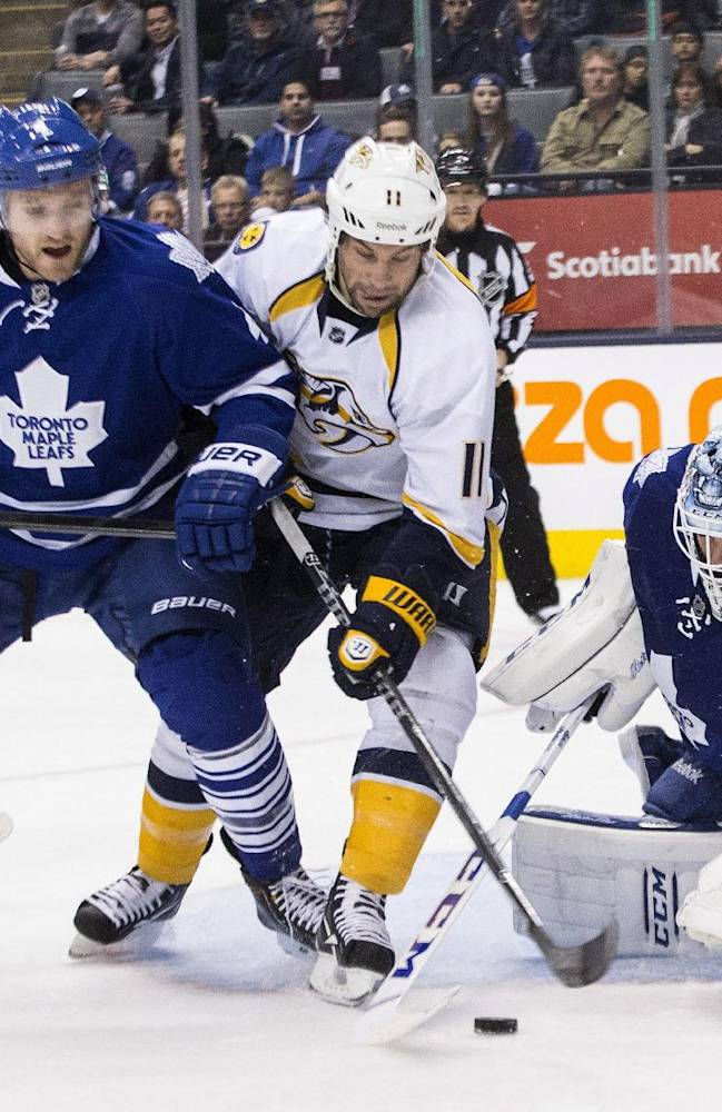 Toronto Maple Leafs goaltender Jonathan Bernier, right, makes a save as Nashville Predators' David Legwand, center, and Leafs' Cody Franson look for a rebound during the first period of an NHL hockey game, Thursday, Nov. 21, 2013 in Toronto