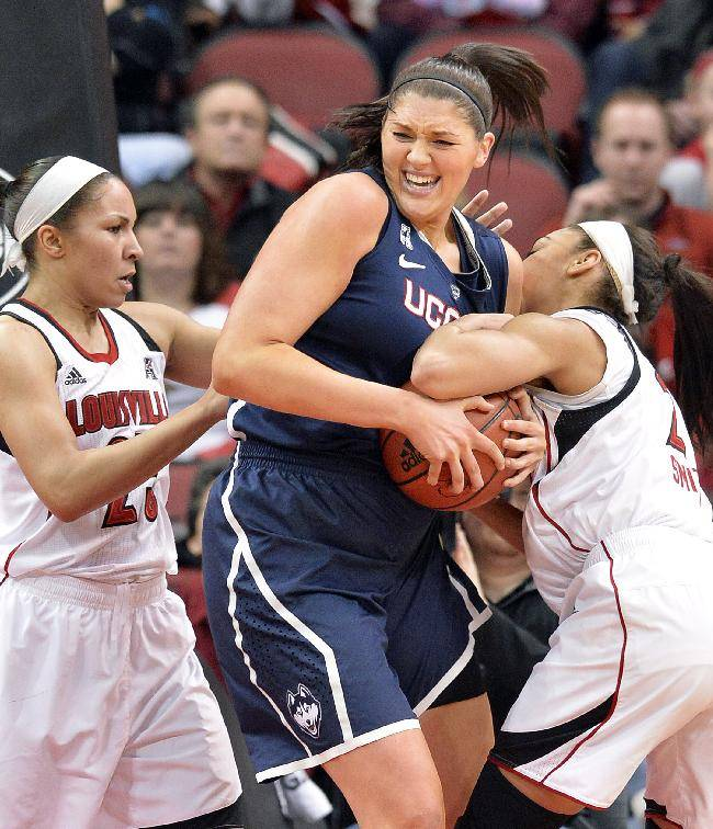 Connecticut's Stefanie Dolson, center, battles Louisville's Tia Gibbs, Left, and Bria Smith for a rebound during the first half of an NCAA college basketball game Monday, March 3, 2014, in Louisville, Ky