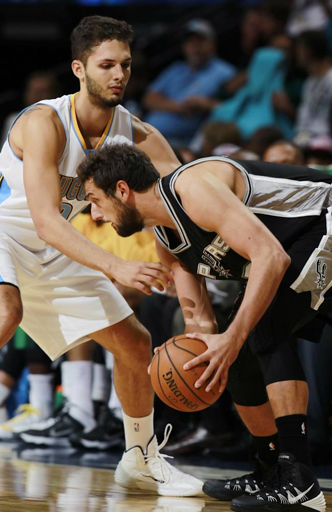 San Antonio Spurs guard Marco Belinelli, right, of Italy, works ball inside against Denver Nuggets guard Evan Fournier, of France, in the first quarter of an NBA preseason basketball game in Denver on Monday, Oct. 14, 2013