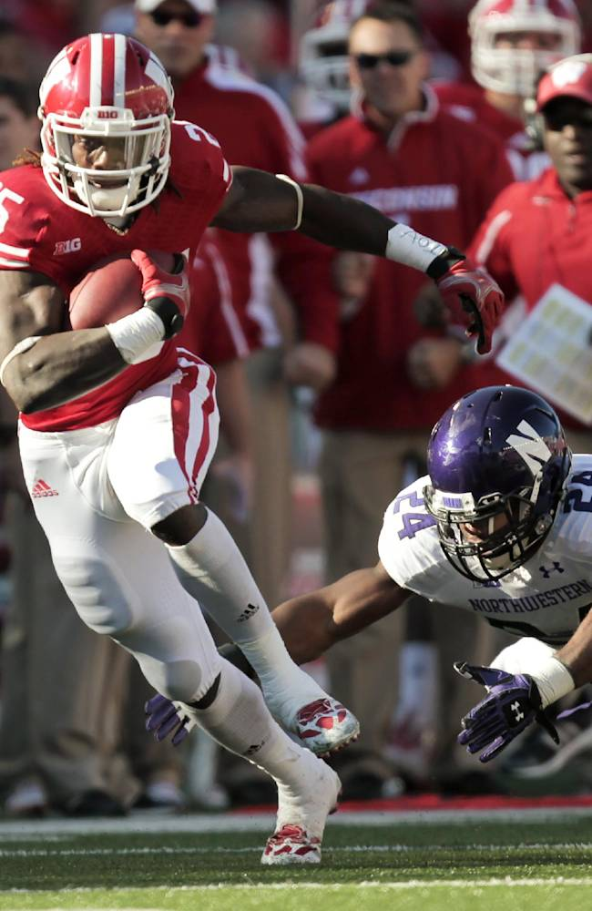 Wisconsin running back Melvin Gordon runs for a first yard against Northwestern safety Ibraheim Campbell during the first half of an NCAA college football game in Madison, Wis., Saturday, Oct. 12, 2013. Wisconsin upset Northwestern 35-6. Gordon had 176 yards