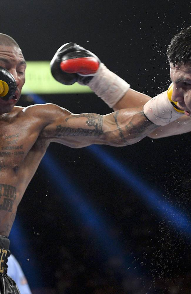 Ashley Theophane, left, lands a punch against Pablo Cesar Cano in the eighth round during a welterweight fight, Saturday, Sept. 14, 2013, in Las Vegas