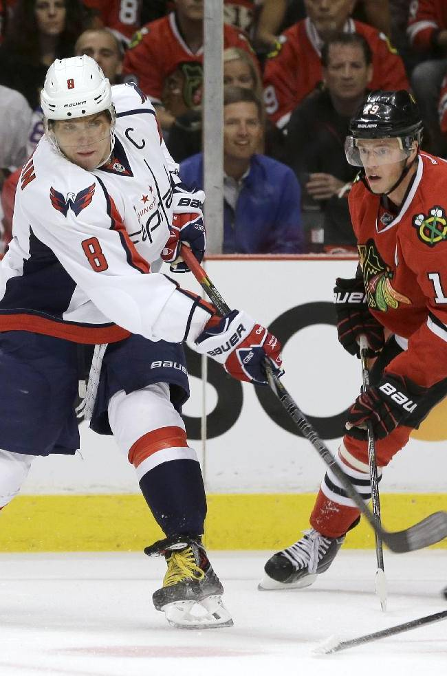 Washington Capitals right wing Alex Ovechkin (8) takes a shot past Chicago Blackhawks center Jonathan Toews (19) during the first period of an NHL hockey game Tuesday, Oct. 1, 2013, in Chicago