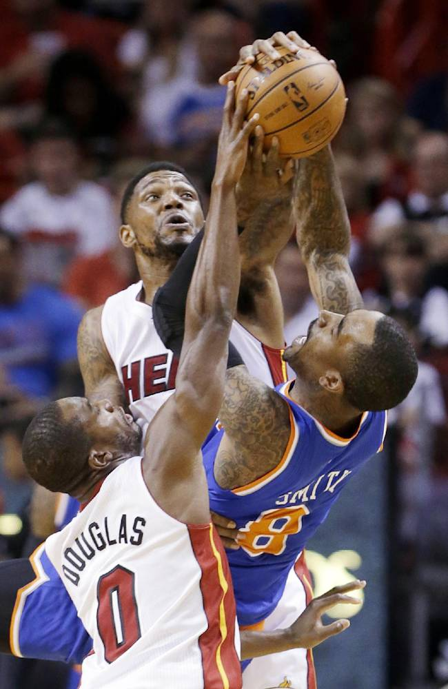 Miami Heat forward Udonis Haslem, rear, and guard Toney Douglas (0) prevent a pass by New York Knicks guard J.R. Smith (8) during the first half of an NBA basketball game, Sunday, April 6, 2014, in Miami