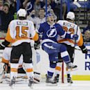 Tampa Bay Lightning right wing Richard Panik, center, of Slovakia, celebrates between Philadelphia Flyers defenders Tye McGinn, left, and Luke Schenn after scoring during the third period of an NHL hockey game Thursday, April 10, 2014, in Tampa, Fla. The