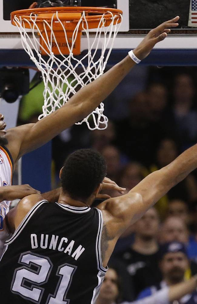 Oklahoma City Thunder forward Kevin Durant (35) attempts to block a shot by San Antonio Spurs forward Tim Duncan (21) in the second quarter of an NBA basketball game in Oklahoma City, Thursday, April 3, 2014