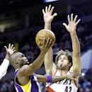 Los Angeles Lakers guard Jodie Meeks, left, goes to the hoop against Portland Trail Blazers center Robin Lopez during the first half of an NBA basketball game in Portland, Ore., Monday, March 3, 2014 The Associated Press