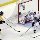 Boston Bruins center Patrice Bergeron (37) scores a goal past Chicago Blackhawks goalie Corey Crawford (50) and defenseman Brent Seabrook (7)during the second period in Game 3 of the NHL hockey Stanley Cup Finals in Boston, Monday, June 17, 2013. (AP Photo/Charles Krupa)