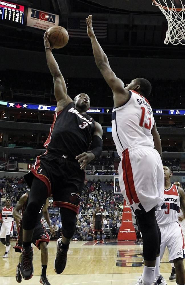 Miami Heat guard Dwyane Wade (3) shoots over Washington Wizards forward Kevin Seraphin (13), from France, in the first half of a preseason NBA basketball game Tuesday, Oct. 15, 2013, in Washington. The Wizards won 100-82