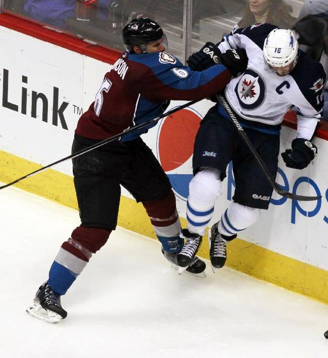 Colorado Avalanche defenseman Erik Johnson, left, checks Winnipeg Jets left wing Andrew Ladd into the boards in the third period of the Avalanche's 3-2 victory in an NHL hockey game in Denver on Sunday, Oct. 27, 2013