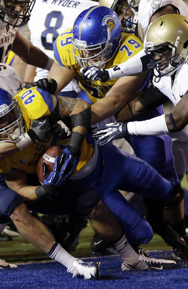 San Jose State running back Jarrod Lawson (40) scores despite the tackle attempt from Navy linebacker Cody Peterson (53) during the first half of an NCAA college football game on Friday, Nov. 22, 2013, in San Jose, Calif