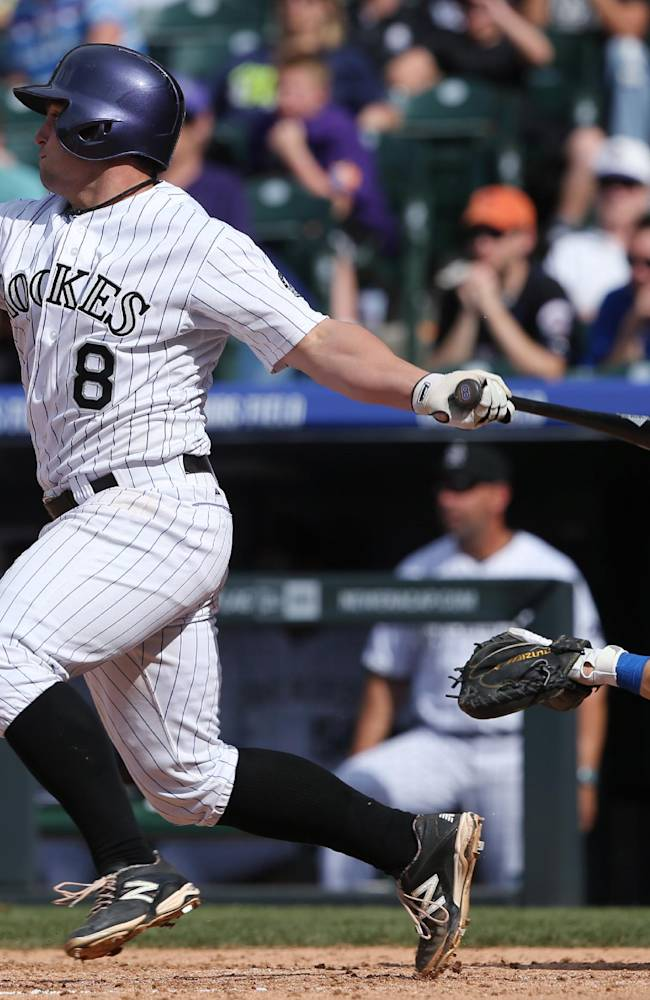 Colorado Rockies' Michael McKenry, left, singles as New York Mets catcher Travis d'Arnaud looks on in the seventh inning of the Mets' 5-1 victory in a baseball game in Denver on Sunday, May 4, 2014