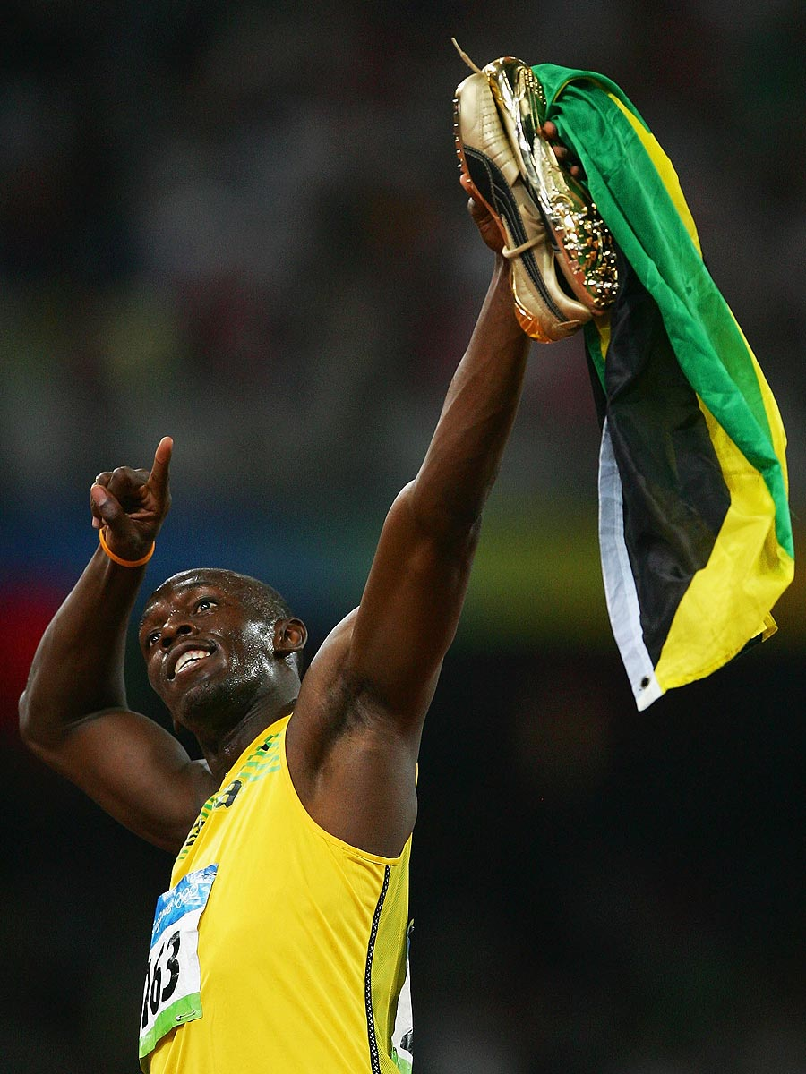 "Usain Bolt strikes his ""to-the-world"" pose after winning gold in the 100 meters. (Getty Images)"