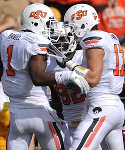 Teammates Isaiah Anderson (center) and Charlie Moore (right) congratulate Oklahoma State running back Joseph Randle on his 59-yard touchdown run during the third quarter.