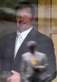 Roger Clemens leaves court Monday as attorney Rusty Hardin is reflected in the glass door. (Getty Images)