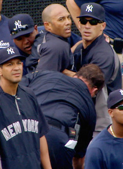Yankees manager Joe Girardi helps Mariano Rivera into a cart after the closer was injured during batting practice. (AP/YES Network)