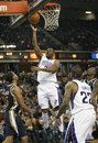 Sacramento Kings guard Marcus Thornton , center, drives to the basket in front of Utah Jazz defender Devin Harris , left, during the second half of an NBA basketball game in Sacramento, Calif., Tuesday, Feb. 28, 2012. The Kings won 103-96.