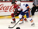 Ottawa Senators defenseman Erik Karlsson battles with New York Islanders right wing Kyle Okposo for control of the puck during an NHL hockey game, Sunday, Feb. 26, 2012, in Ottawa, Ontario. The Senators won 5-2.