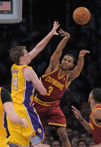 Cleveland Cavaliers Point Guard Ramon Sessions, Right, Passes The Ball As Los Angeles Lakers Power Forward Troy Murphy