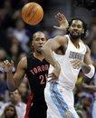 Denver Nuggets center Nene, of Brazil, right, passes around Toronto Raptors center Jamaal Magloire (21) during the fourth quarter of a NBA basketball game on Friday, Jan. 27, 2012, in Denver. Denver won 96-81.