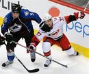 Colorado Avalanche defenseman Shane O'Brien , left, pushes Carolina Hurricanes center Tim Brent , right, in the third period of an NHL hockey game on Friday, Feb. 10, 2012, in Denver.  The Avalanche won 4-3 in overtime.